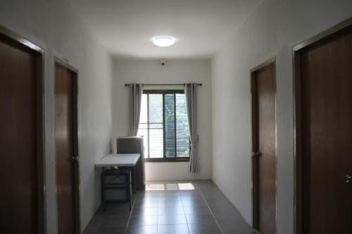 Hallway showing guest refrigerator and doors to 4 rooms.